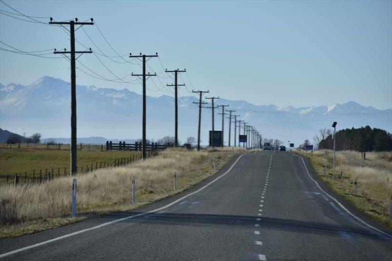 まっすぐな道と並行するどこまでも続く電柱